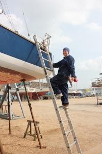 Kass climbing aboard Zest with a drill in Medina Yard